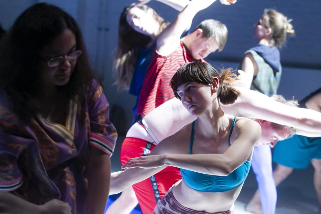 Szenenfoto aus einer Auffuehrung: Mehrere tanzende Personen auf einer Bühne