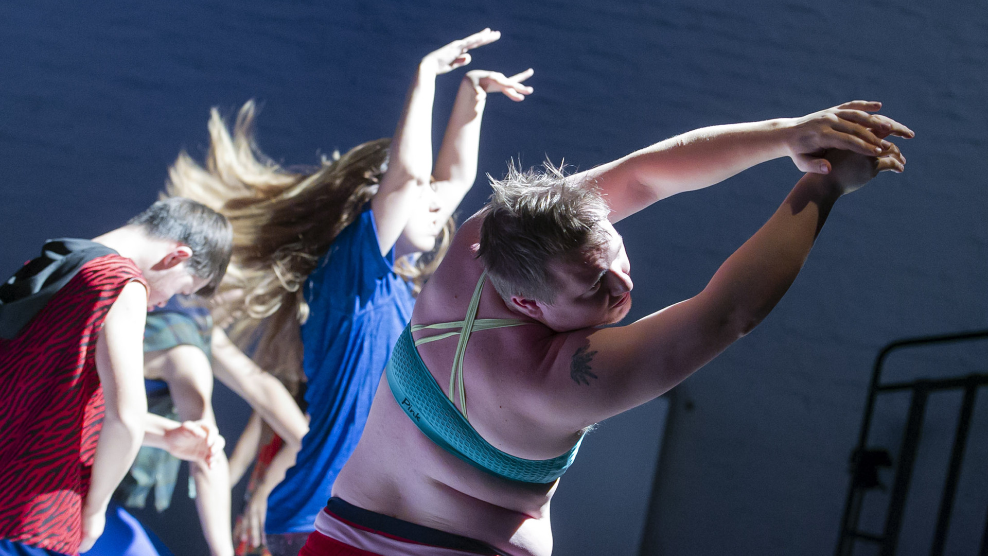Szenenfoto aus einer Auffuehrung: Ein Mann im Vordergrund tanzend. Im Hintergrund drei weitere Personen