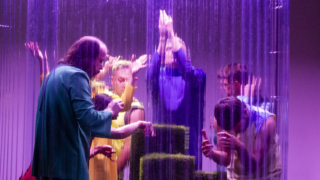 Scene photo of a performance: A couple of people behind a glass