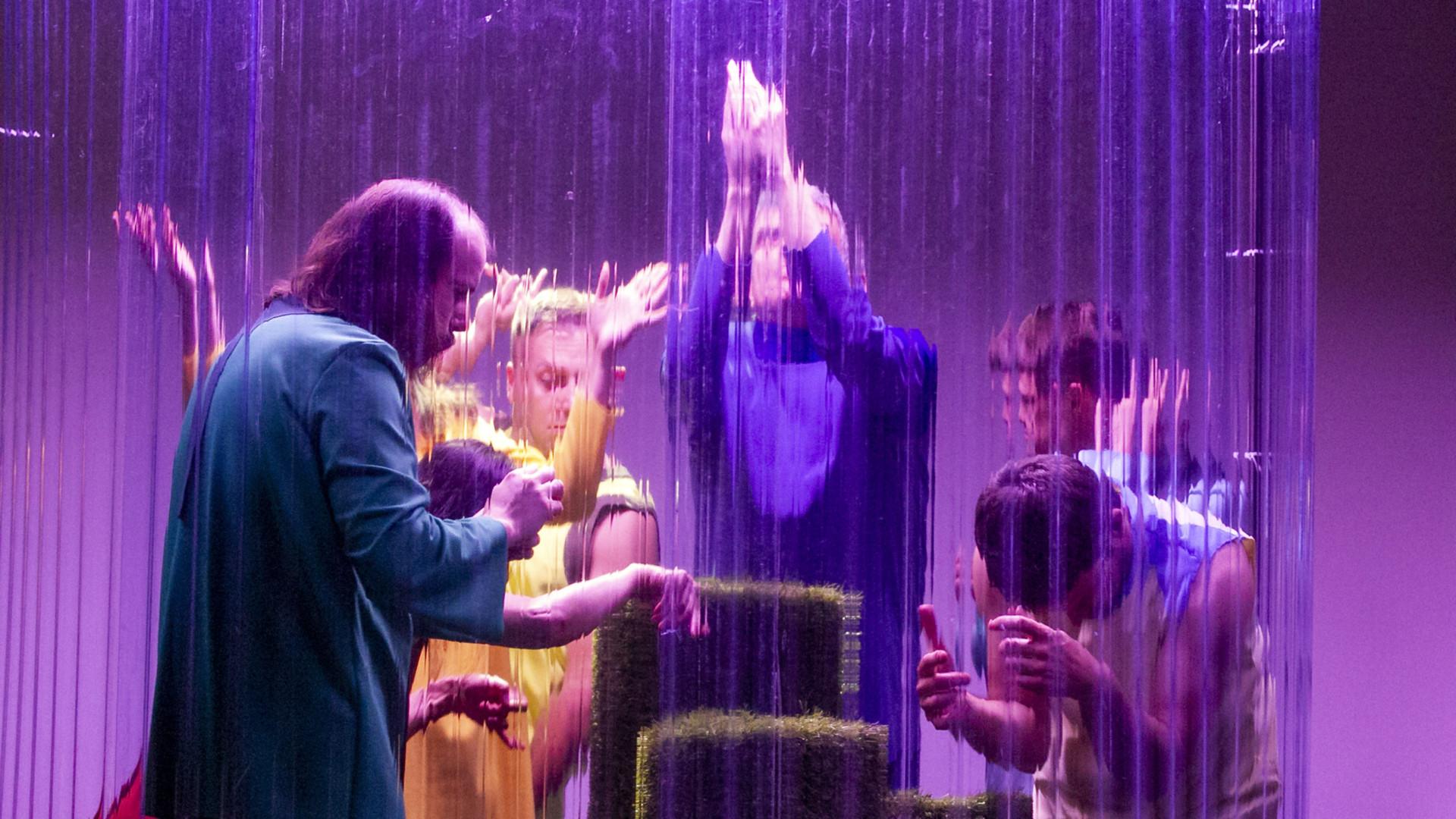 Szenenfoto aus einer Auffuehrung: Mehrere Personen hinter einer Art Glasscheibe auf der Bühne.