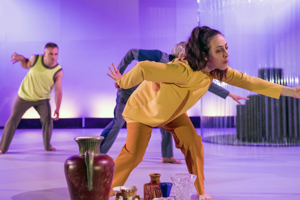 Scene photo of a performance: Three people dancing on a stage. Vases in front of them.