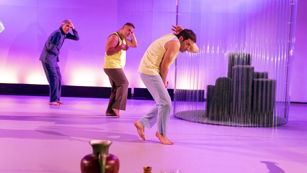 Szenenfoto aus einer Auffuehrung: Drei Männer stehen auf einer Theaterbühne. Im Vordergrund sind Vasen. Im Hintergrund eine Art Gewächshaus.