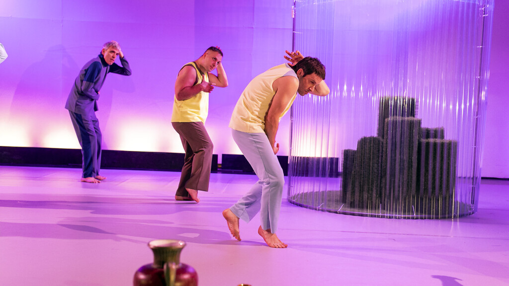 Scene photo of a performance: a couple people behind a glassScene photo of a performance: Three men stand on a stage. In the background is a green house.
