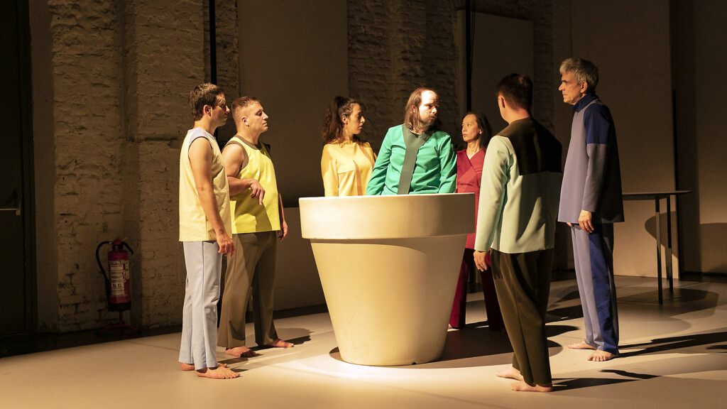 Scene photo of a performance: A couple people stand around a flower pot. one is in the flower pot.