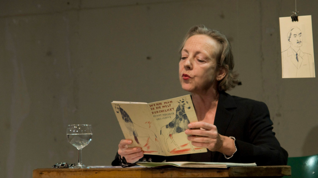 Scene photo of a performance: One woman is reading a newspaper on a stage.