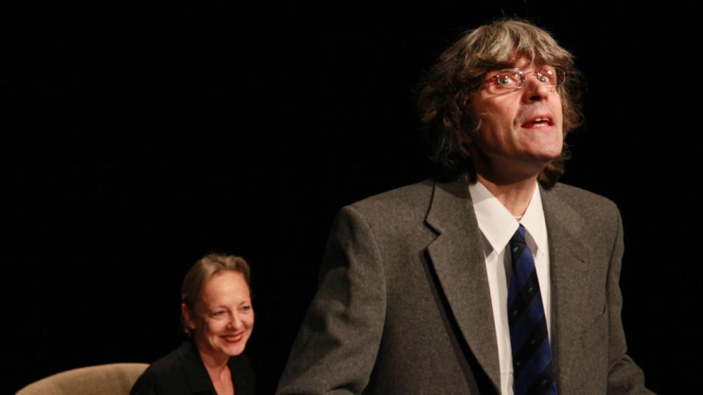 Szenenfoto aus einer Auffuehrung: Ein Mann im Vordergrund auf einer Buehne. Eine Frau sitzt im Hintergrund.