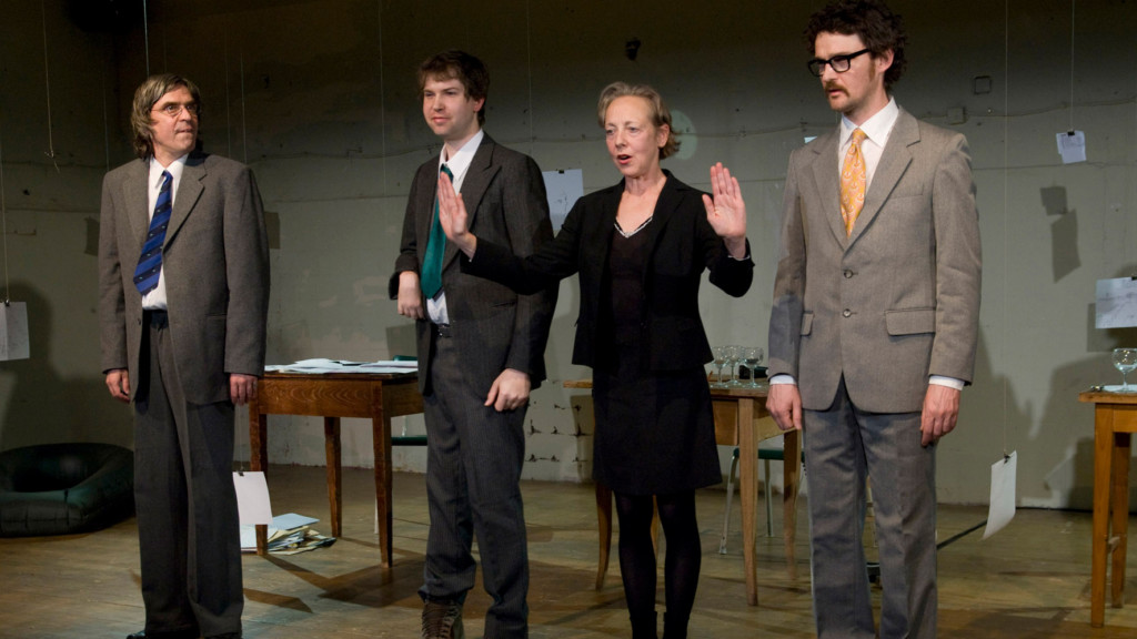Scene photo of a performance: Four people stand next to each other on a stage.