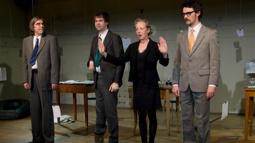 Szenenfoto aus einer Auffuehrung: Vier Personen stehen auf einer Theaterbuehne nebeneinander.