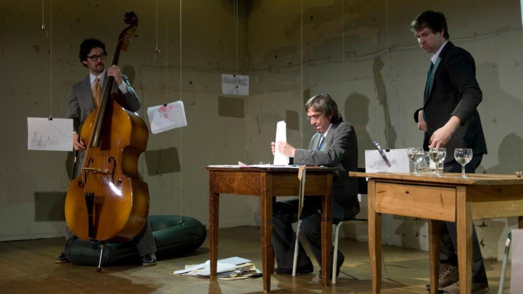 Szenenfoto aus einer Auffuehrung: Links ein Mann mit Kontrabass. Rechts daneben sitzt und steht jeweils ein Mann an einem Holztisch.