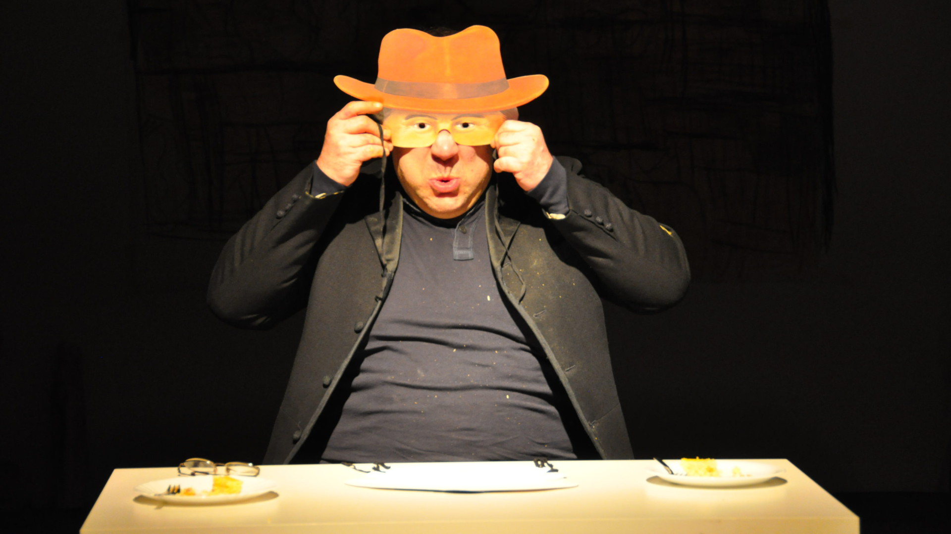Szenenfoto aus einer Auffuehrung: Ein Mann sitzt an einem Tisch auf einer Theaterbühne und hält sich eine Maske vor das Gesicht.