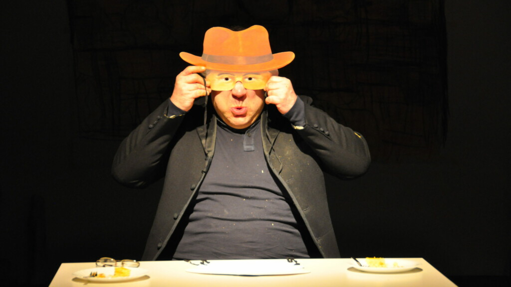 Photo from a performance: A man sits at a table on a theater stage and holds a mask in front of his face.