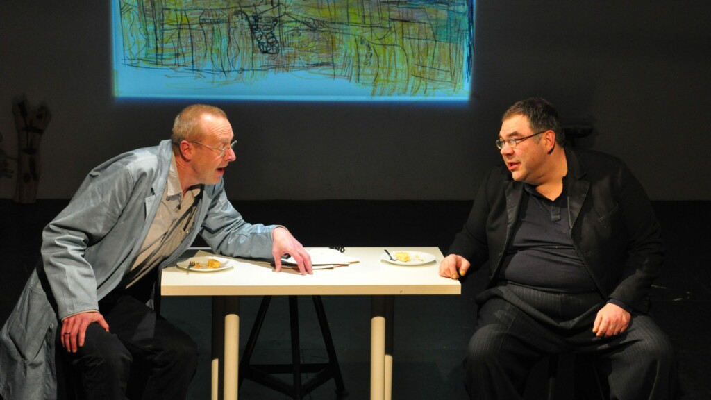 Photo from a performance: Two men converse on a table on a stage.