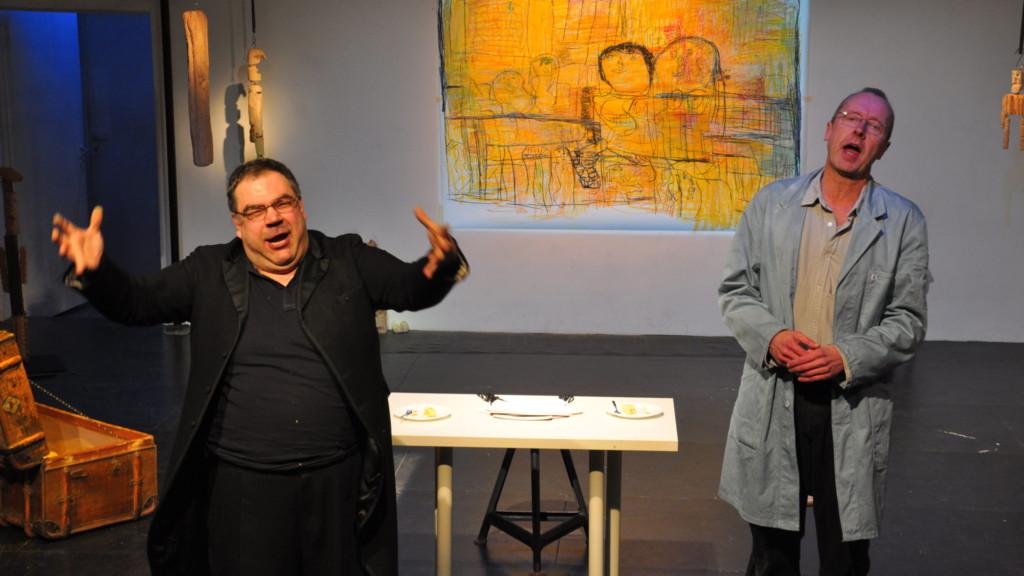 Szenenfoto aus einer Auffuehrung: Zwei Männer auf einer Theaterbühne. Im Hintergrund ein Tisch und eine Leinwand.