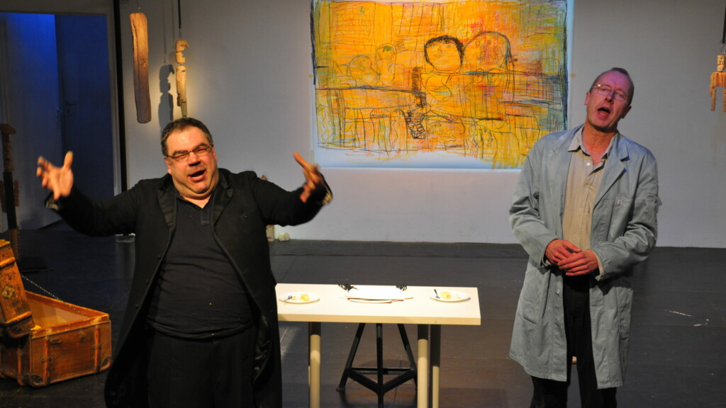 Photo from a performance: Two men on a theater stage. In the background a table and a canvas.