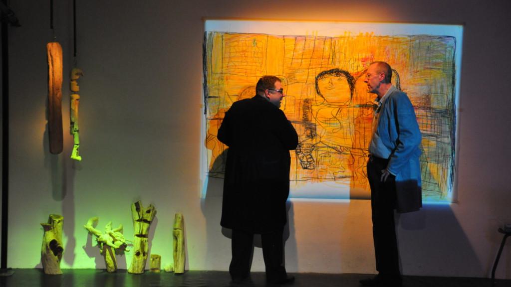 Szenenfoto aus einer Auffuehrung: Zwei Männer vor einer Leinwand auf einer Theaterbühne.