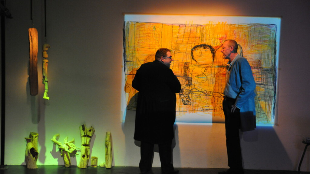 Photo from a performance: Two men in front of a canvas on a stage.