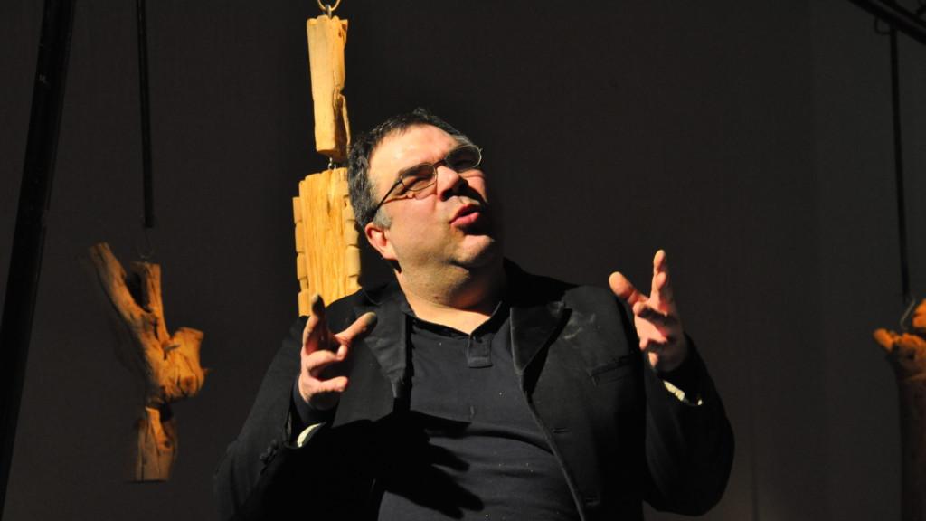 Szenenfoto aus einer Auffuehrung: Ein Mann erzählt etwas auf einer Theaterbühne.