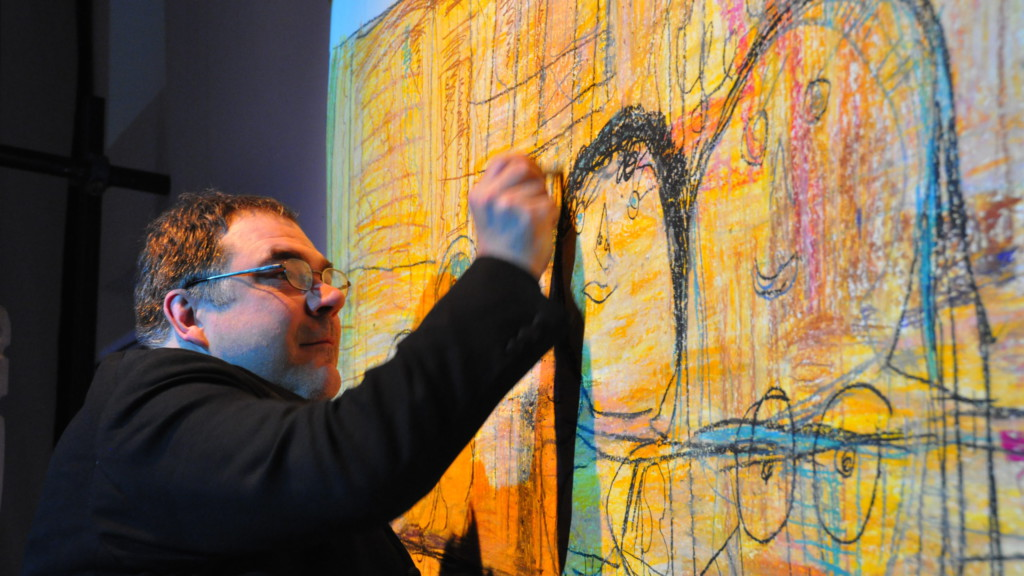Szenenfoto aus einer Auffuehrung: Ein Mann vor einer Leinwand auf einer Theaterbühne.