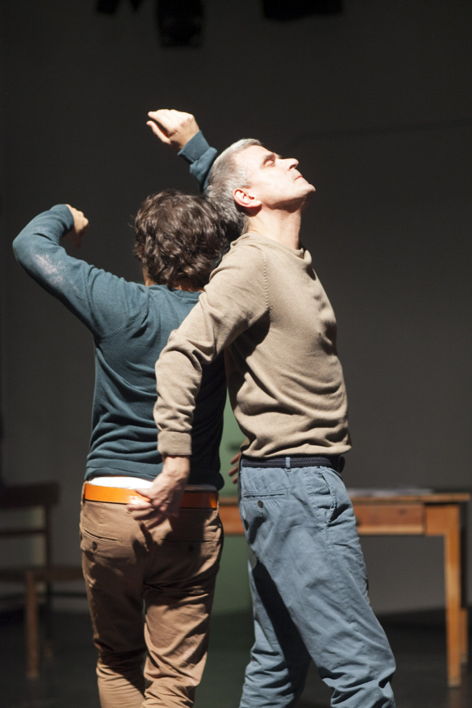 Scene photo of a performance: Two men back to back on a stage.