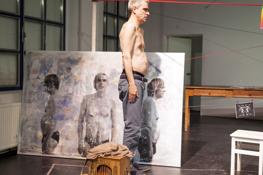 Scene photo of a performance: A man with closed eyes in front of a canvas on a stage.