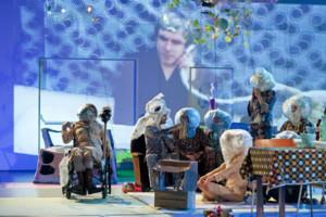 Szenenfoto aus einer Auffuehrung: Mehre Personen mit bunten Kostuemen auf einer Bühne