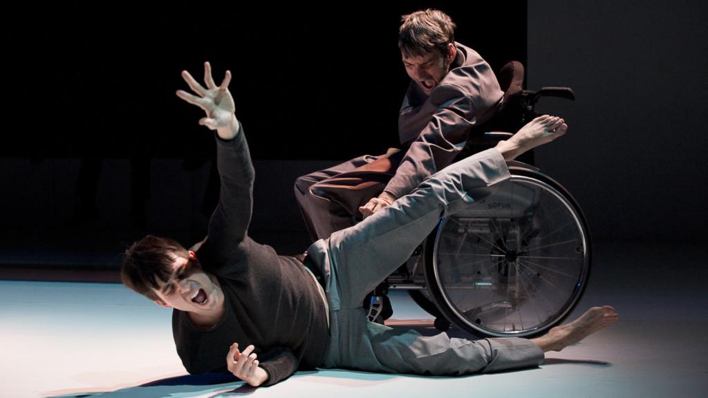 Szenenfoto aus einer Auffuehrung: Zwei Männer schreien. Einer liegt auf dem Boden, der andere sitzt im Rollstuhl und zeigt auf den Liegenden.