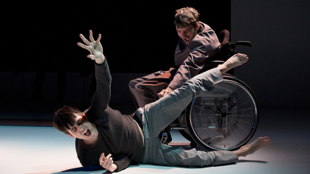 Scene photo of a performance: One men in a wheelchair on a stage. Another one is laying on the ground in front of him.