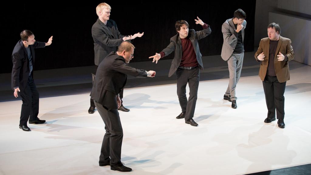 Szenenfoto aus einer Auffuehrung: Sechs Männer in Anzügen stehen auf einer Theaterbühne.