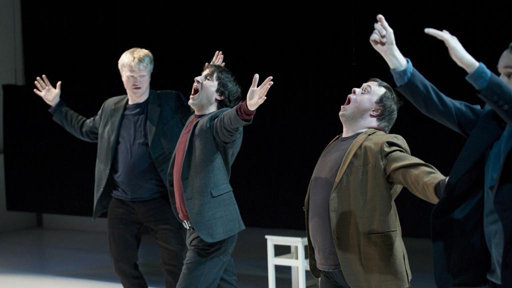 Szenenfoto aus einer Auffuehrung: Vier Männer in Anzügen mit ausgebreiteten Armen. Zwei davon mit geöffnetem Mund in Anzügen.