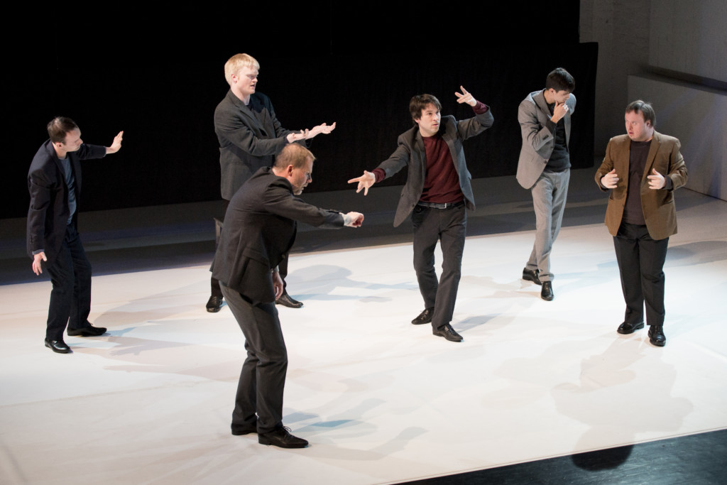 Scene photo of a performance: Six men in a suit on a stage.