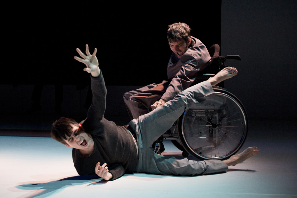 Scene photo of a performance: Two men are screaming. One is lying on the ground. The other one is in a wheelchair.