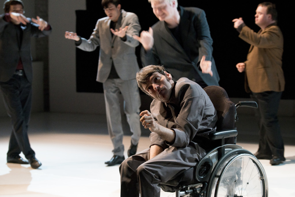 Scene photo of a performance: Five men on a stage. One is in a wheelchair. The other four blurred in the background.