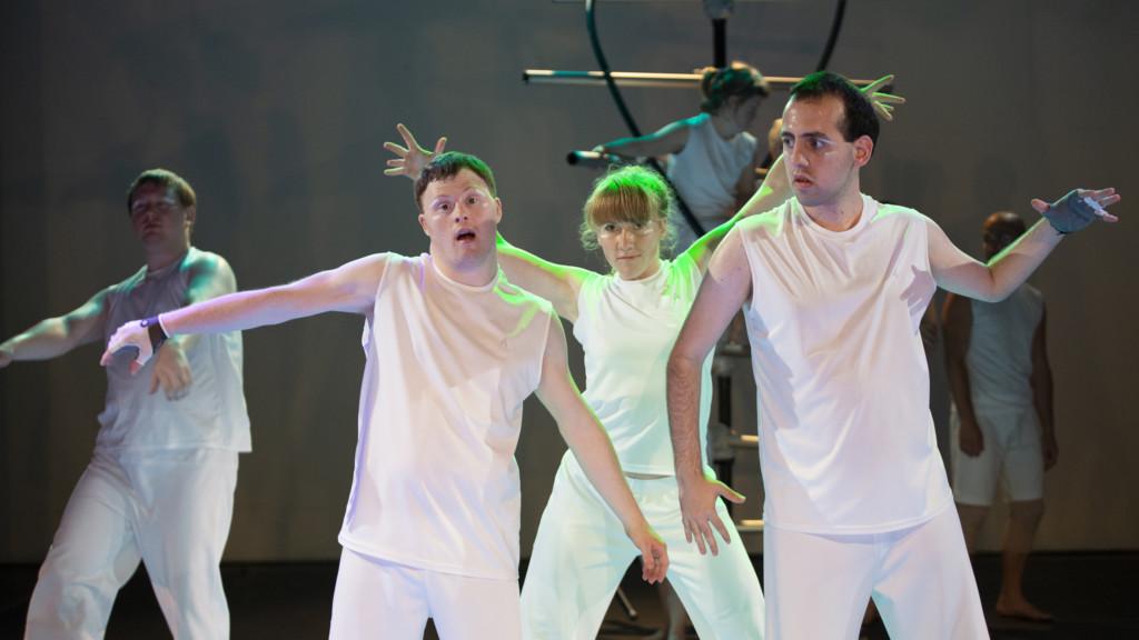 Szenenfoto aus einer Auffuehrung: Vier Personen auf einer Theaterbuehne. Im Hintergrund eine DNA-Nachbildung.