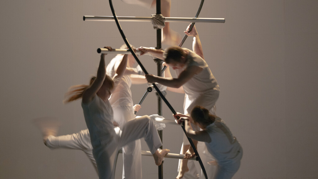 Scene photo of a performance: Four people on a DNA object an a stage.