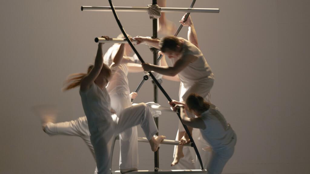 Szenenfoto aus einer Auffuehrung: Fuenf Personen stehen auf einer DNA-Nachbildung auf einer Theaterbuehne.