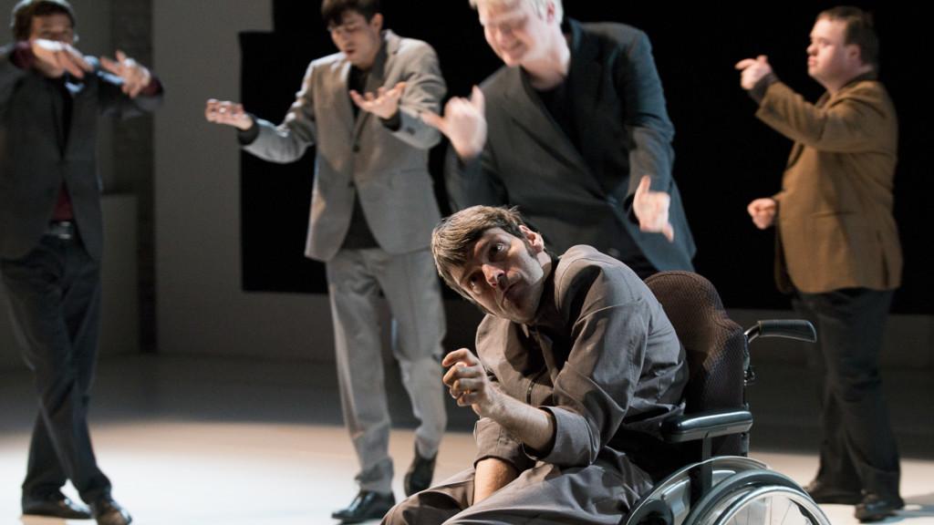 Szenenfoto aus einer Auffuehrung: Fünf Männer auf der Bühne. Einer davon im Rollstuhl vorn. 4 verschwommen im Hintergrund.