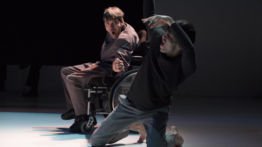 Szenenfoto aus einer Auffuehrung: Zwei Männer auf einer Theaterbühne. Einer im Vordergrund kniend. Der Mann im Hintergrund sitzt im Rollstuhl.