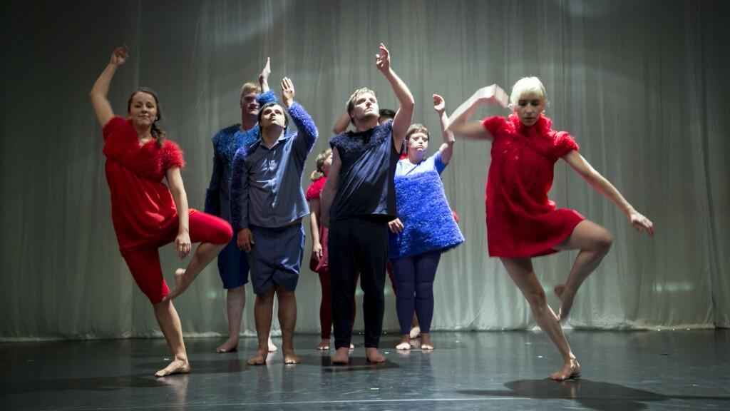 Szenenfoto aus einer Auffuehrung: Mehrere Personen tanzen und stehen auf einer Buehne.