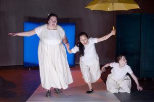 Szenenfoto aus einer Auffuehrung: Drei Frauen auf der Bühne. Zwei stehen und eine kniet.