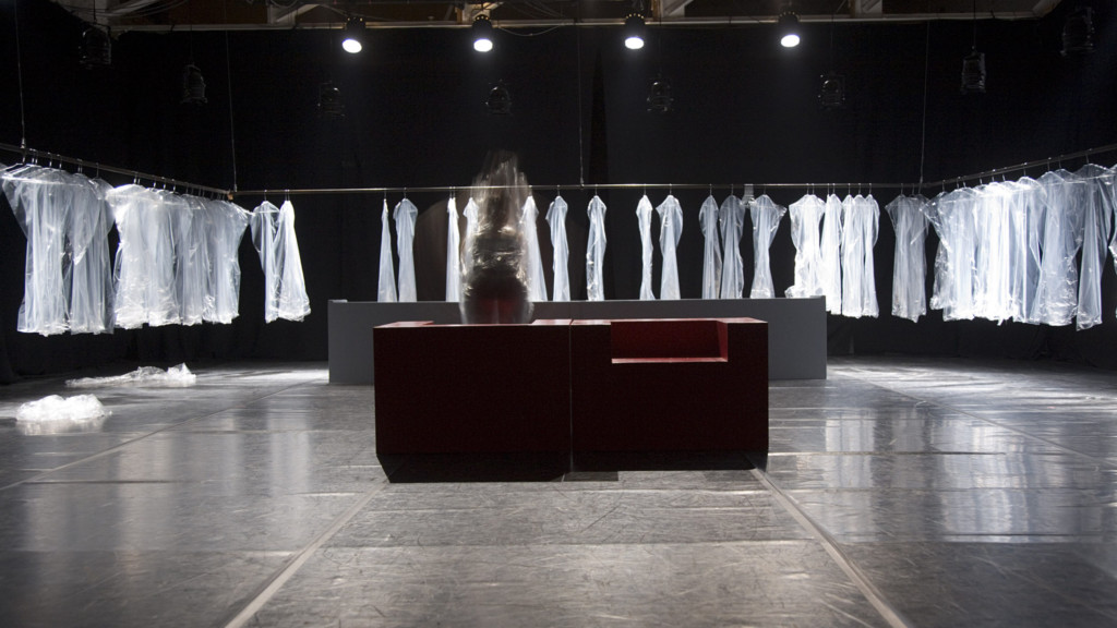 Szenenfoto aus einer Auffuehrung: Zwei Sessel in der Mitte. Ringsherum Kleider auf einer Kleiderstange.