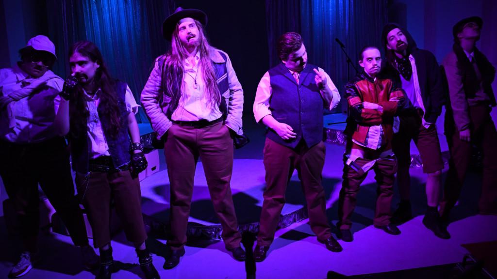Szenenfoto einer Auffuehrung: Mehrere Personen stehen in einer Reihe auf einer Theaterbuehne nebeneinander.