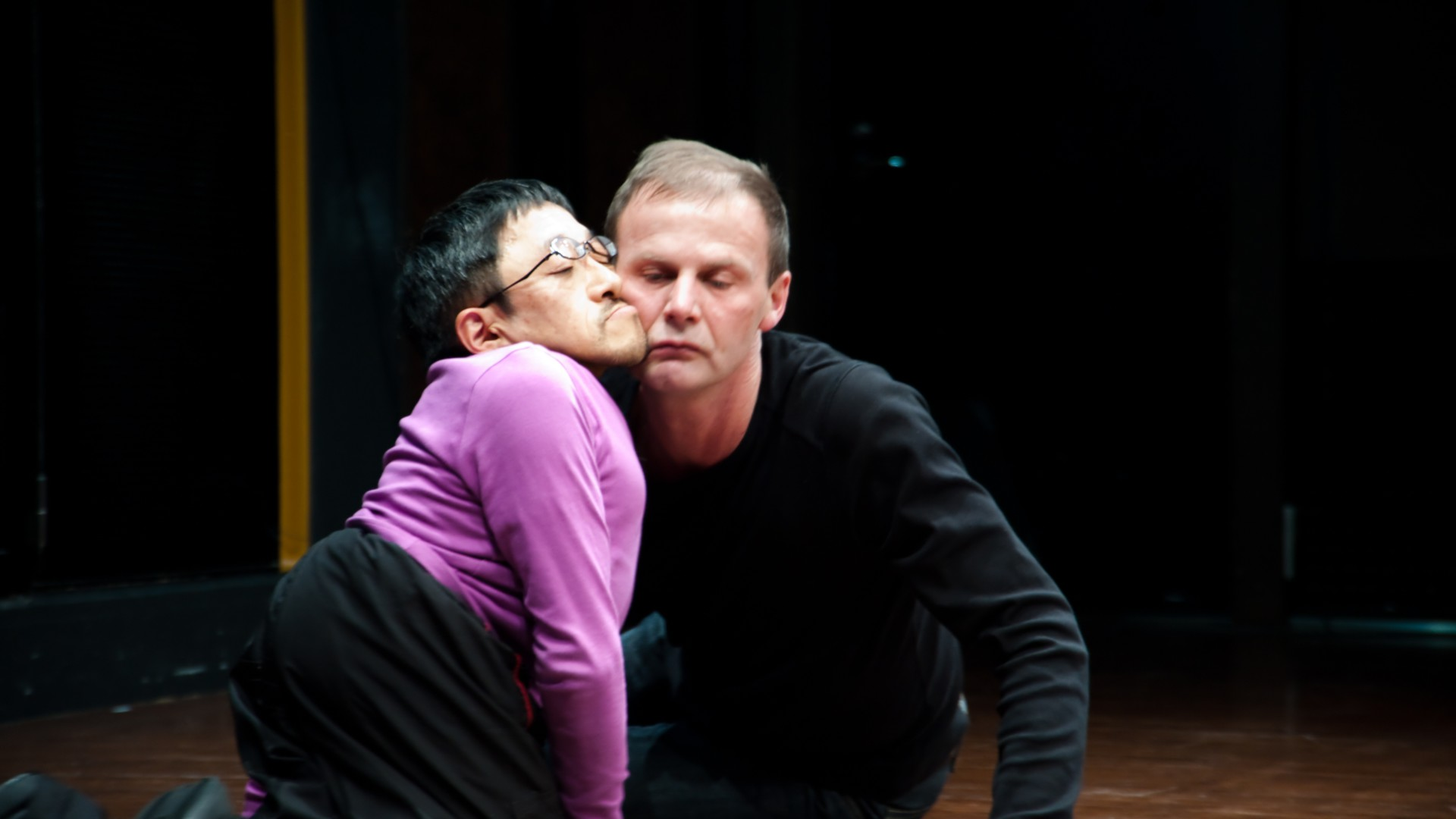 Scene photo of a performance: Two men are sitting on the ground with closed eyes.