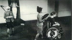 Szenenfoto aus einer Auffuehrung: Vier Menschen auf der Bühne. Im Vordergrund schiebt eine Frau mit Fächer eine andere Frau im Rollstuhl. Links daneben steht ein Junge mit fragender Geste. Im Hintergrund kommt jemand mit Strohhut aus einer Tür.