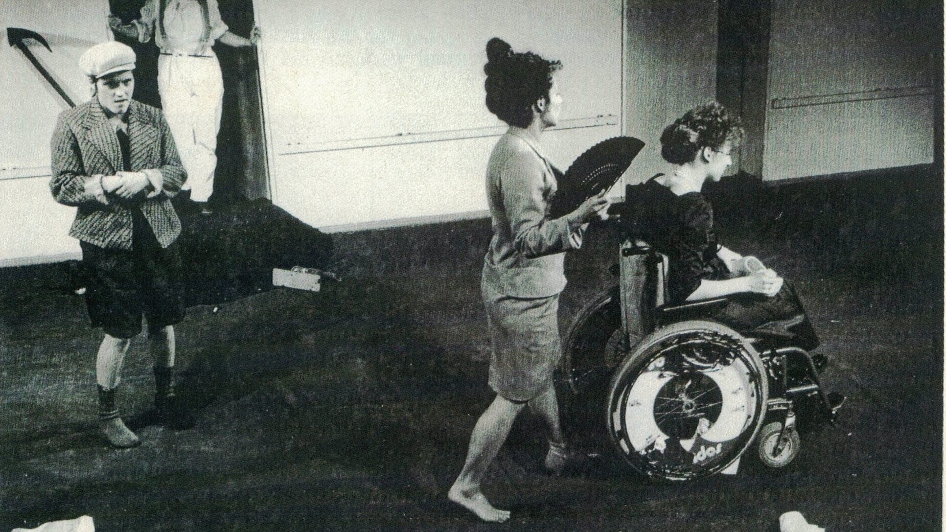 Scene photo of a performance: Four people on a stage. One in a wheelchair.