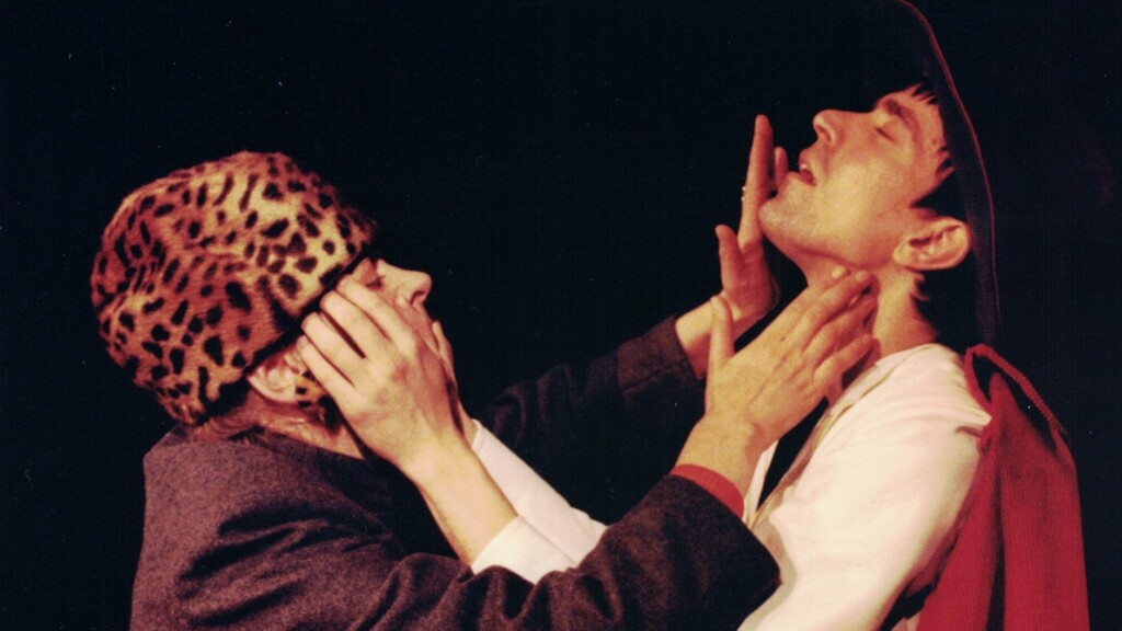 Scene photo of a performance: One woman and a men on a stage touching each others face.