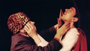 Szenenfoto aus einer Auffuehrung: Eine Frau mit Tigerfellkappe und ein Mann berühren gegenseitig ihre Gesichter.n