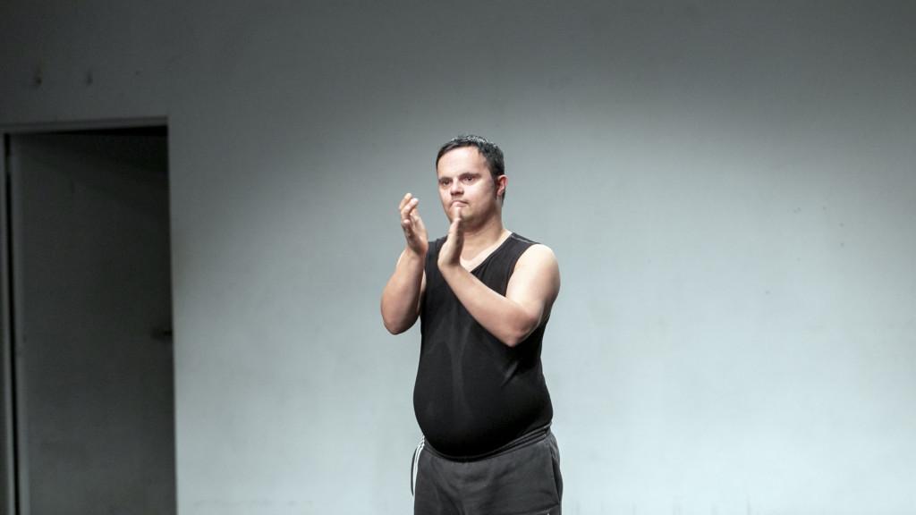 Szenenfoto einer Auffuehrung: Mann auf einer Theaterbuehne klatscht.