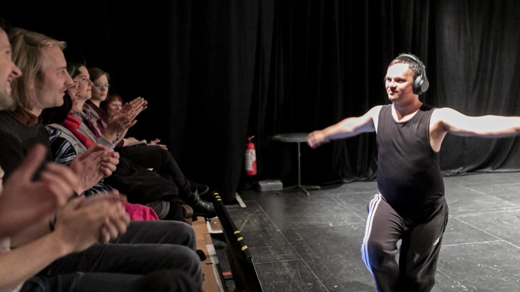 Szenenfoto einer Auffuehrung: Mann auf einer Theaterbuehne mit Kopfhörern. Vor Ihm das Publikum.