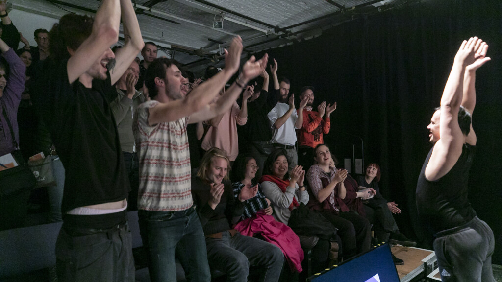 Scene photo of a performance: An audience clapping enthusiastically.