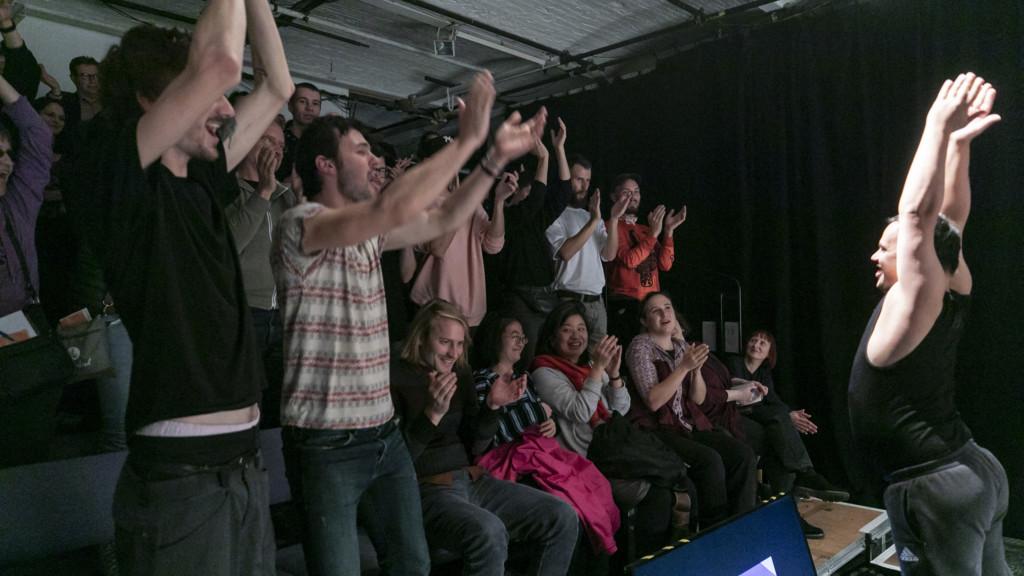 Szenenfoto einer Auffuehrung: Publikum mit hochgerissenen Armen.